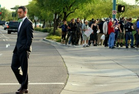A man walks by an American Legislative Exchange Council (ALEC) protest in Phoenix, Wednesday, Feb. 29, 2012. (Photo/Kendra Yost)