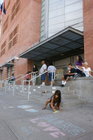 """A young girl colors on the ground with chalk at a """"Chalk the Police"""" event Oct. 1, 2011. (Photo/Kendra Yost)"""
